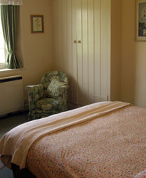view of the double bedroom with green and white arm chair and double bed