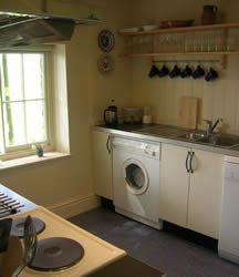 View of the kitchen with washing machine, sink and shelves with crockery and glasses