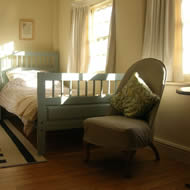 sunny top bedroom with low chair and painted single bed